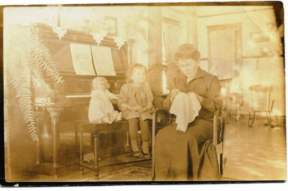 a Postcard with lady and needlework by piano AC