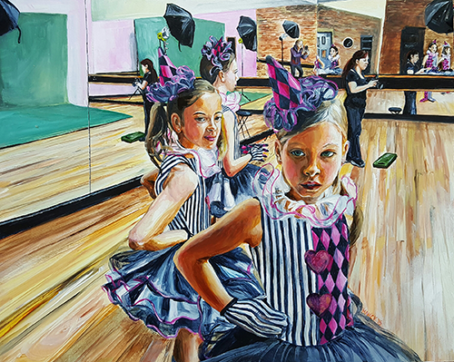 2 young ballerinas in black, white and pink harlequin tutu costumes await their turn to be photographed in a dance studio.