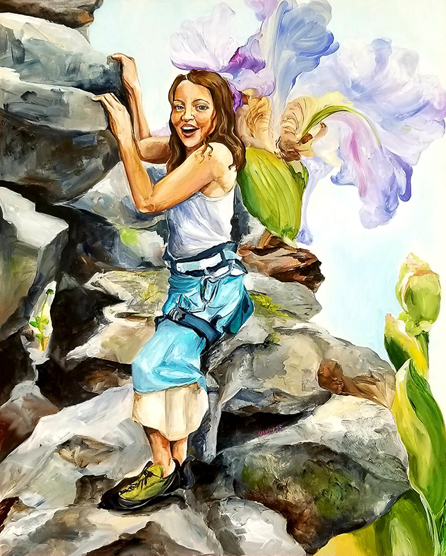 A 10-year-old girl in a skirt and white tank top with a climbing harness grips rocks with her hands. She smiles brightly with an overgrown iris rising behind her.