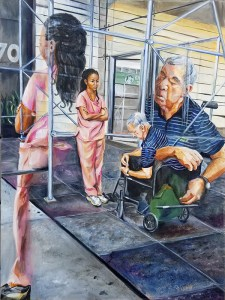 A nurse in peach colored scrubs leans against the scaffolding watching her elderly male patient in his wheel chair struggle to retrieve something from his green bag on the side of his chair.