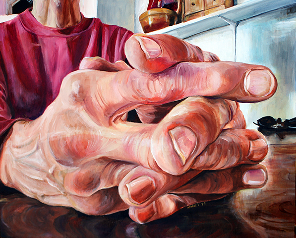 A pair of hands with fingers entwined, rest on a highly polished, dark wooden table. In the background the burgundy shirt and neck of the subject are visible, as are a shelf with kitchen items and a pair of sunglasses.