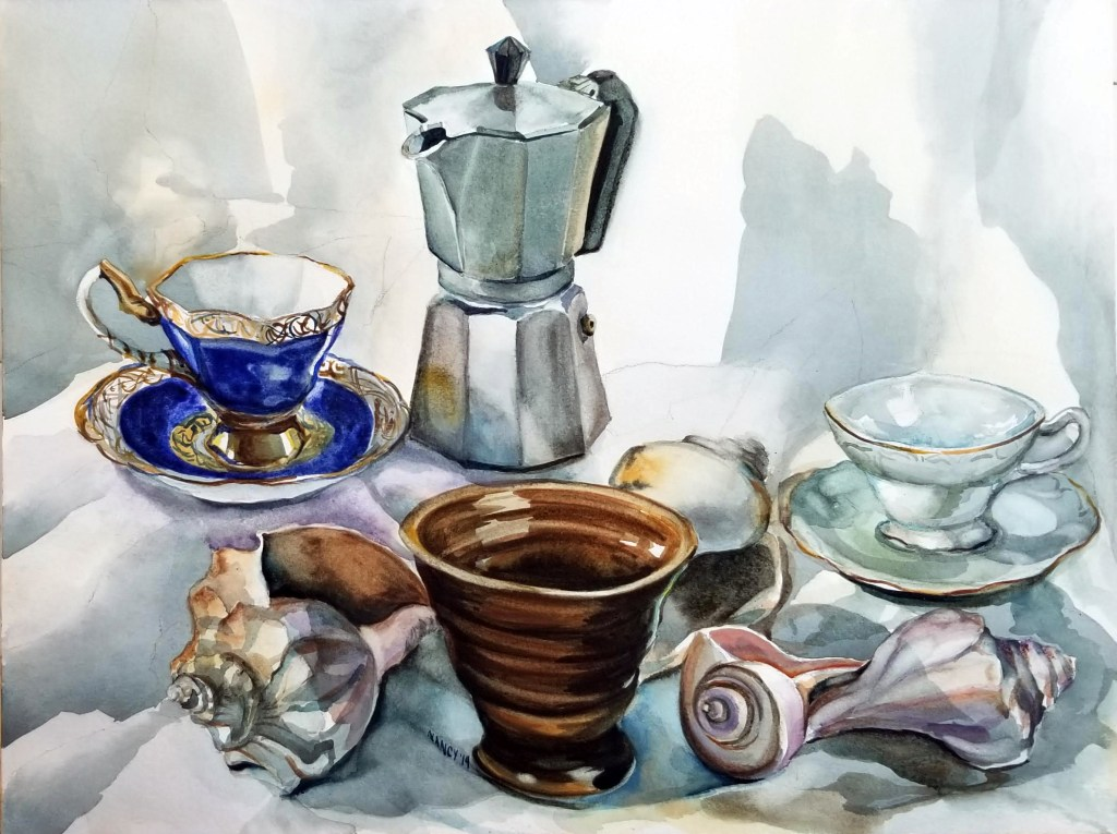 A still life of shells, 3 porcelain tea cups in bright blue, white and deep brown tenmoku glaze, and a bialetti coffee pot set against a white sheet.