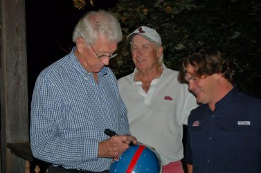 "Coach Billy Brewer autograph's Wes Ehrhardt's prized powder blue Ole Miss helmet, while Jimmy Sandifer looks on. No doubt The Dog's smile results from finding a new friend ""fit for making an old one out of!"""