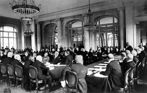This old black and white photograph shows participants in the 1919 Paris Peace Conference meeting in the Hall of Mirrors in the Palace of Versailles.