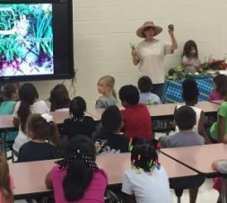"On Friday, August 26, first grade students at New Albany Elementary School invited local gardener Kelly Coltharp to share how she grows vegetables, herbs, and flowers and participates in the local Farmers' Market. Coltharp shared a PowerPoint that showed how food goes from a garden to a farmers market. She also shared pictures and information about the local Biscuits and Jam Farmers Market. The story of the week for the first graders was ""Farmer's Market"" and the focus question was ""What can we see around our neighborhood?"""
