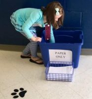 Lilly Hester, a first grade student in Mrs. Christy Littlejohn's class, helps gather paper products to be recycled.