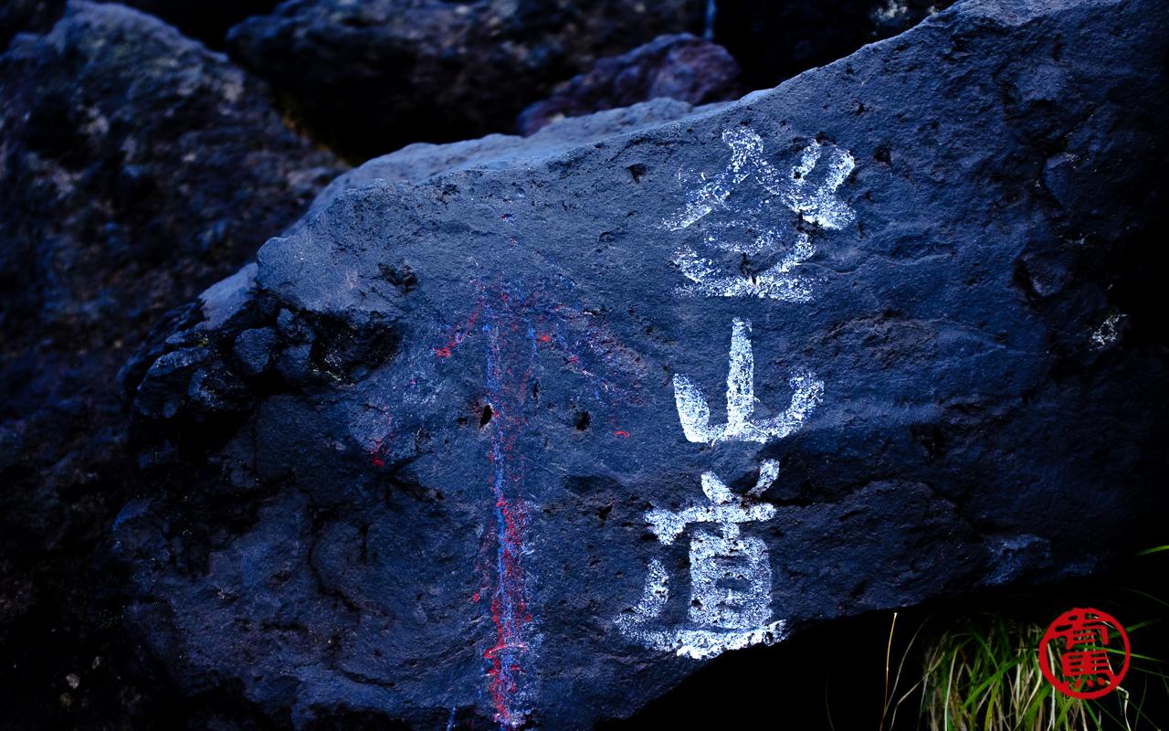 Antiga sinalização da trilha em japonês escrito: caminho para subir a montanha.