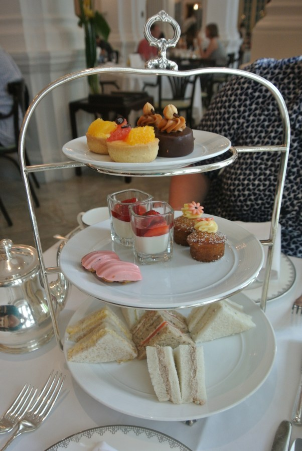 Three tier tray full of finger sandwiches and petit fours.