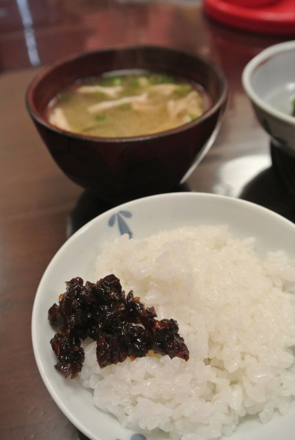 A traditional Japanese breakfast includes a bowl of white rice. Here I eat it with tsukudani.