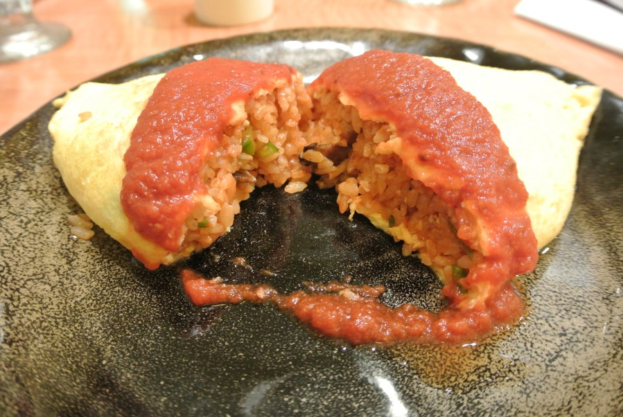 Omu-rice filled with tomato sauce fried rice.