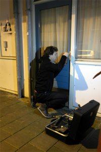 Slotenmaker Daan Numan forceert de keukendeur van Cailine Kuit. (Foto: Friso Weijers)