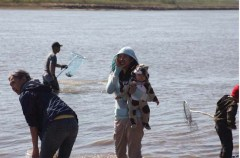 Peter Nook fishes while Lisa Phillips and Jaylene Pitka (with baby) tend to matters on shore.