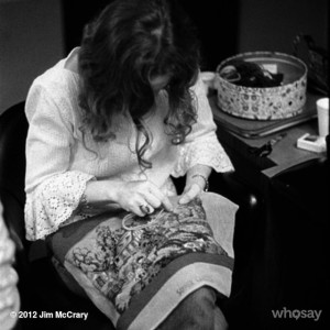 photo of Carole King stitching the needlepoint that was on the Tapestry album cover, copyright unknown from wesay.com