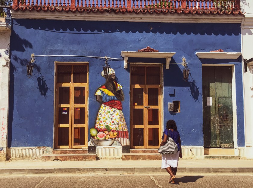 Mom walking across the street in Cartagena in a blue shirt and white skirt going towards a blue wall with a palenquera selling fruits painted on it