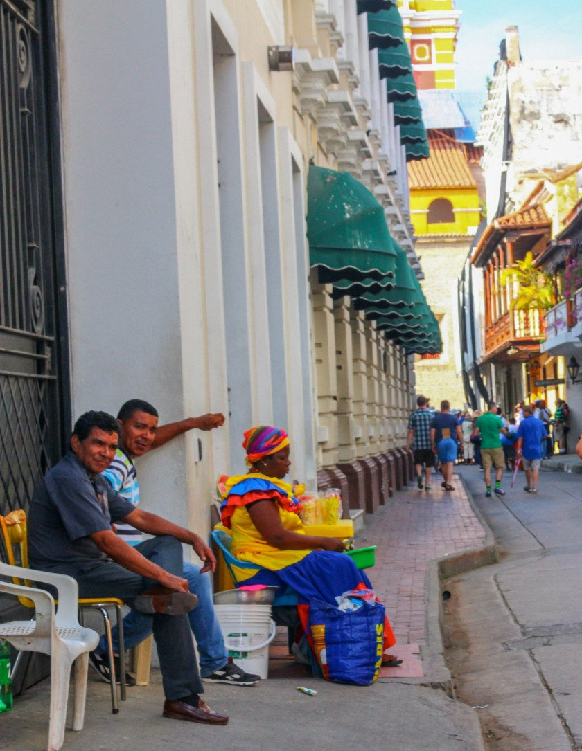 palenquera woman in bright dress sitting in downtown Cartagena street with two Colombian men next to her. She's selling wrapped mangoes.