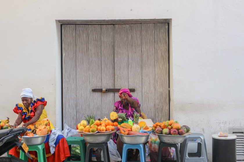 two palenquera women sitting down infront of white washed wall with piles of colorful fruit in front of them. They are both in bright traditional palenque outfits