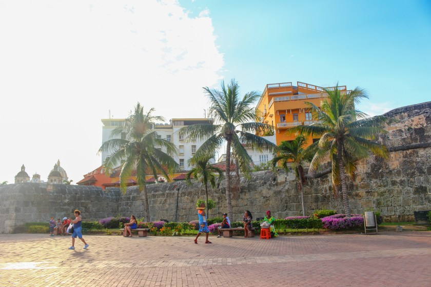 golden hour against the fort of Cartagena. A palenquera in bright green sells candies, a man walks past with greenery on his head and there are 3 large palm trees in the foreground