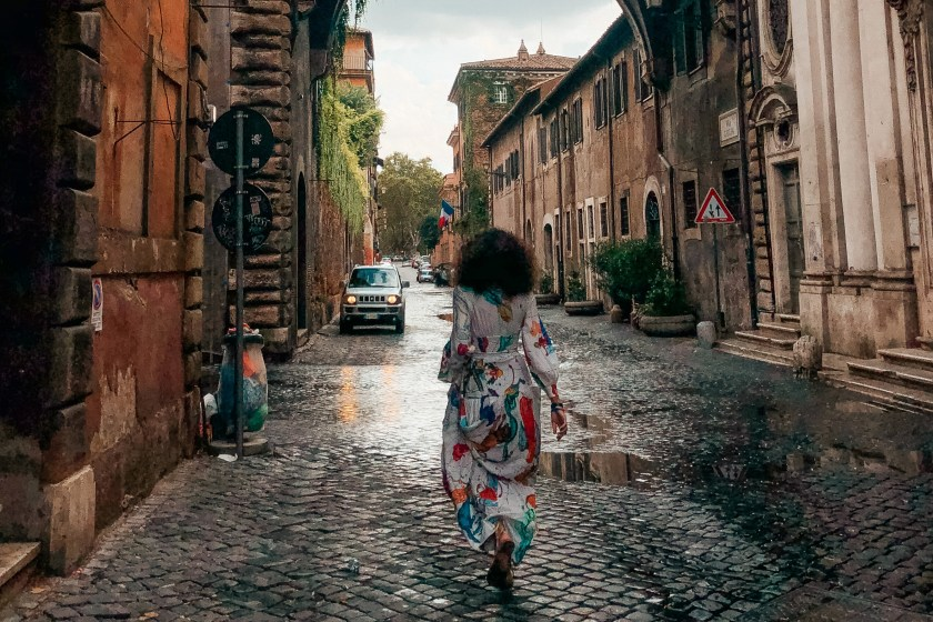 Stella walking down a raining street in Rome