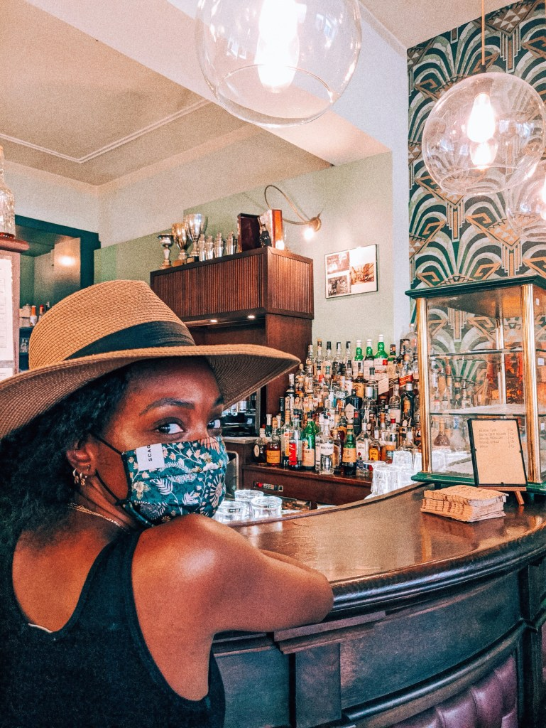 Women with mask on inside a bar