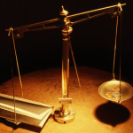 photo of balance scale with money on one side and contract on the other