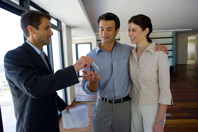 Young couple receiving new house keys from a real estate agent