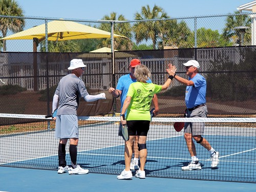 four pickleball players on court