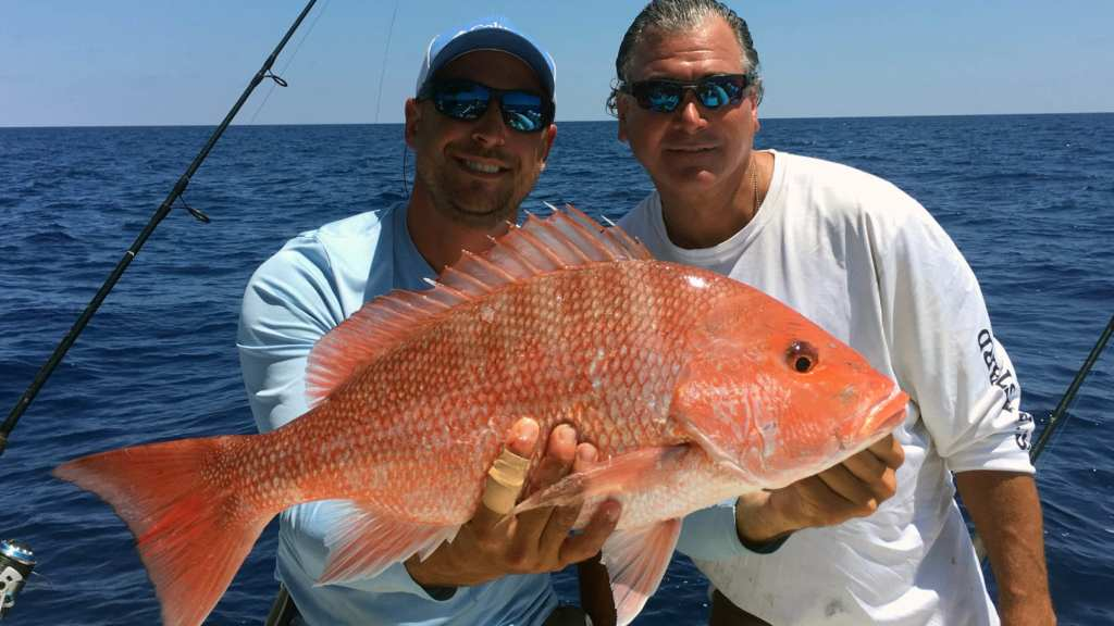 two fisherman deep sea fishing for red snapper in naples, florida