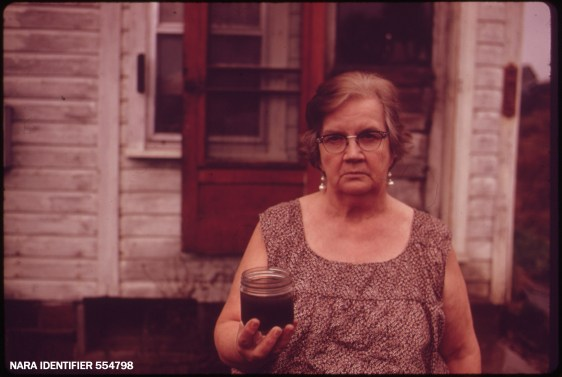 Mary Workman holds a jar of undrinkable water...