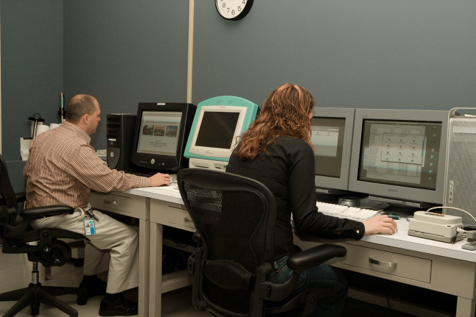 Two National Archives staff members seated in front of four computer screens in the digital lab.