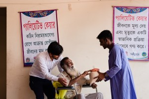 Patient Montaj Uddin Sheikh takes his food package from PCA Mehedul Hasan, while Field Coordinator Md. Saiful Hoque assists with his wheelchair. Photo credit: Sakib Pratyay and Juthika Dewry.