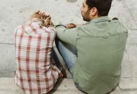 man and woman sitting on sidewalk, obsessief ex syndroom