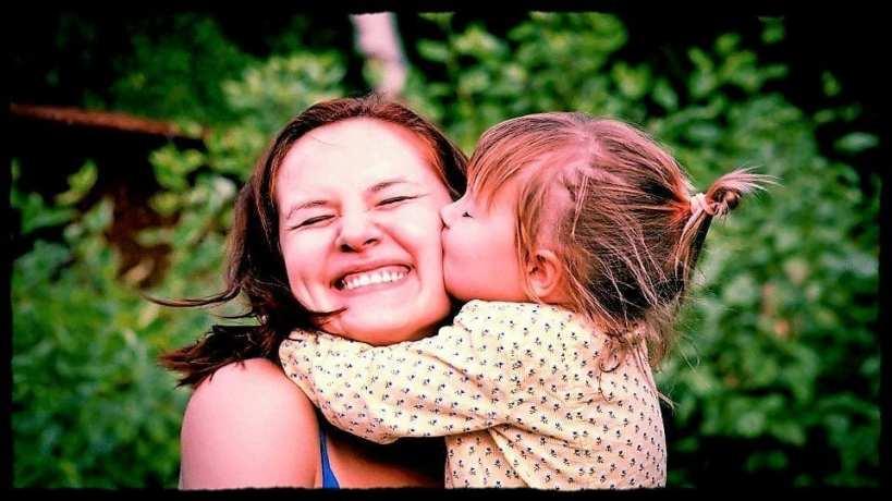 foto van kindje dat kusje geeft aan zijn mama