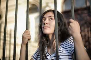 sad isolated young woman looking away through fence with hope, mishandeling van CVS patiënten door een narcist.