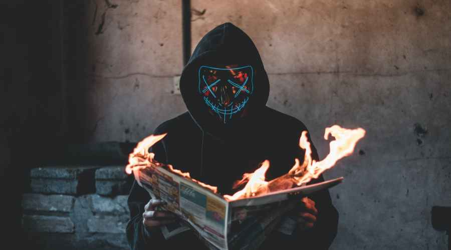 person holding a burning news paper close up photography