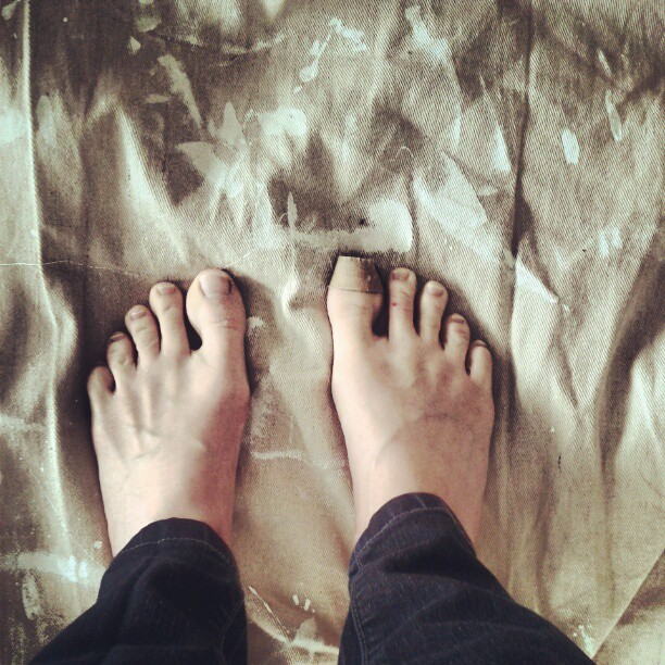 a photo of laurel green's bare feet on a tarp and there is a bandaid on her right big toe