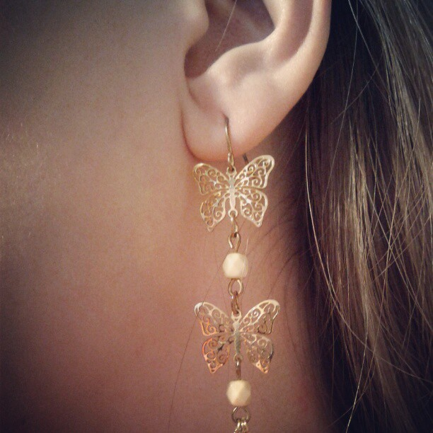 a photo of one of laurel green's ears with a butterfly earring in it