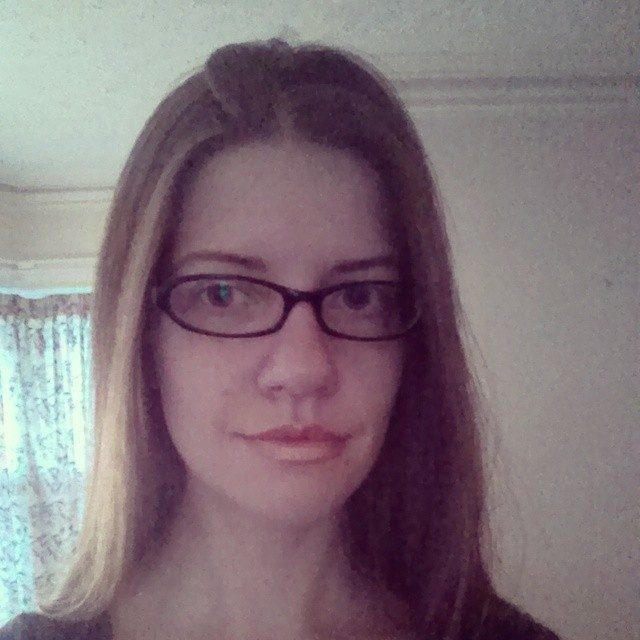a photo of laurel green's face, she is wearing glasses and smirking