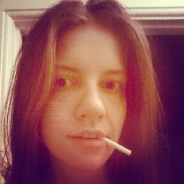 a photo of laurel green's face with a popeye cigarette in her mouth