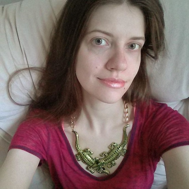 a photo of laurel green wearing a crocodile necklace
