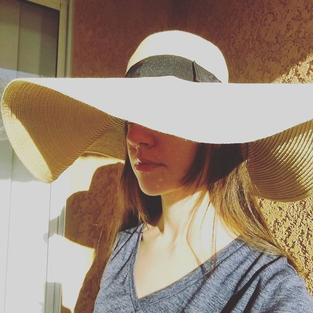 a photo of laurel green wearing an oversized sun hat