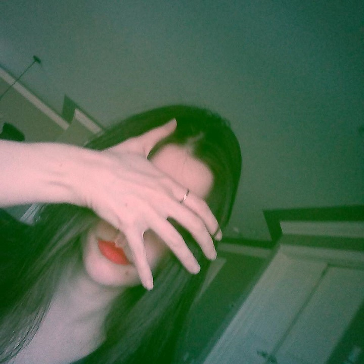 photo of laurel green covering her face and wearing red lipstick