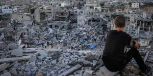 202471_a_palestinian_child_sits_above_the_ruins_of_his_ruined_home1