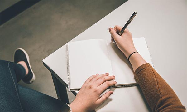 Image montrant une personne écrivant un lipogramme