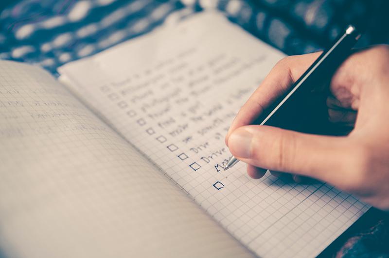 Une personne cochant des cases d'une liste (symbolisant les différents types de comparatifs)