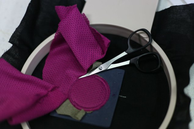 Place any fabric on top to insulate the conductive fabric. Cut away all the extra fabrics around the edge of the button.