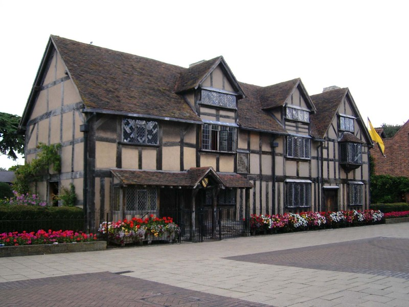Photograph of a half-timbered Tudor-style house with two floors and three gables with colorful flowers planted in front
