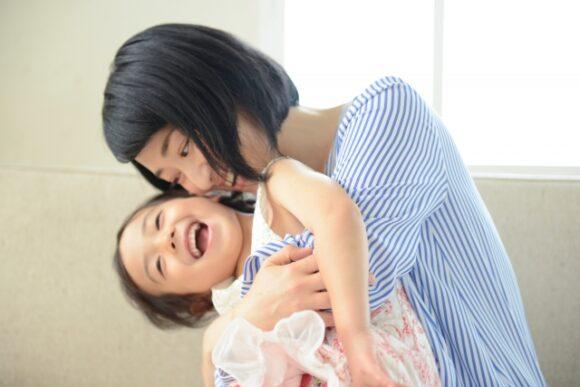 子供を後ろから抱きかかえ笑顔の母親