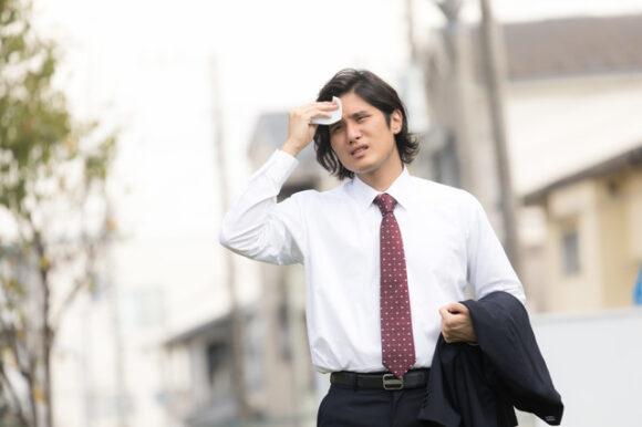 額の汗を拭う男性