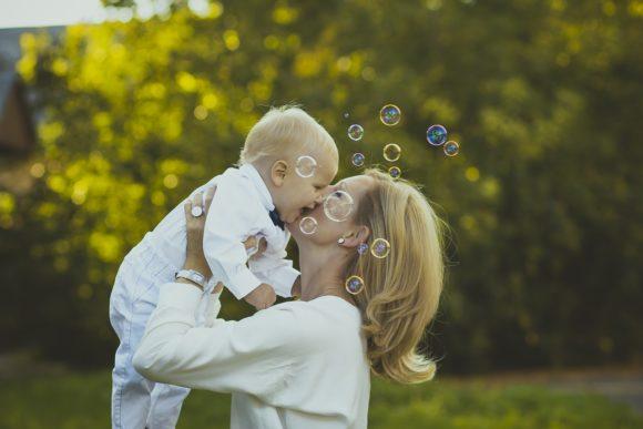 笑顔で赤ちゃんを抱き上げるママ
