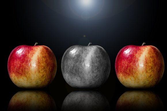 赤いりんご2個に挟まれた灰色のりんご